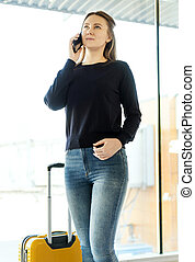 Young woman with mobile phone in the airport.