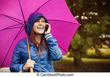 Young woman with mobile phone on rainy day