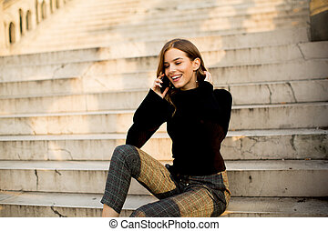 Young woman with mobile phone sitting at stairs outdoor