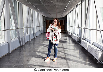 Young woman with mobile phone standing in airport hall