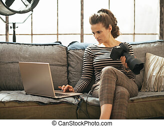 Young woman with modern dslr photo camera using laptop in...