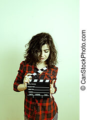 Young woman with movie clapper board vintage color effect