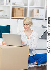 woman with moving boxes looking at laptop