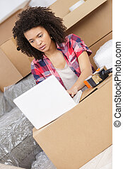 young woman with moving boxes looking at laptop