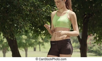Young woman with mp3 player in park - Sports activity, ...