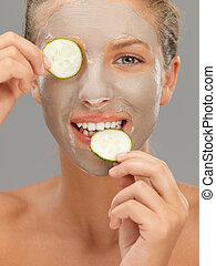 young woman with mud mask cucumber slices