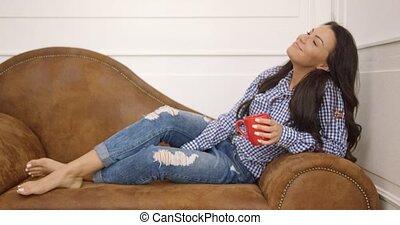 Young woman with mug on sofa