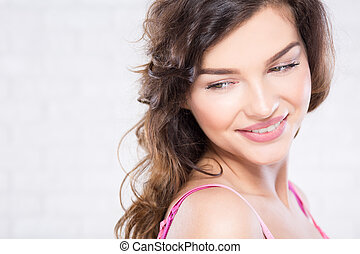 Young woman with natural make up smiling sheepeshly