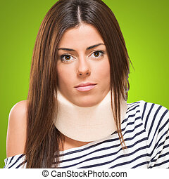Young woman with neck brace against a green background