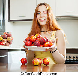 Young woman with nectarines