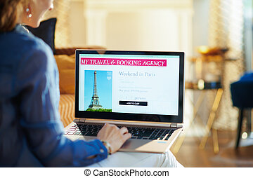 young woman with online travel site on laptop