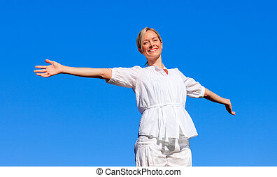 Young woman with open arms outdoors
