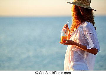 Young woman with orange juice in disposable cup against the sea