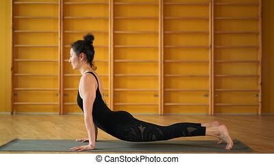 Young woman with oriental appearance practicing yoga alone...