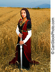 Young woman with ornamental dress and sword in hand  standing on a wheat field with sunset. Natural background..
