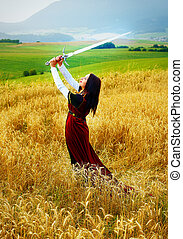 Young woman with ornamental dress and sword in hand  standing on a wheat field with sunset. Natural background.