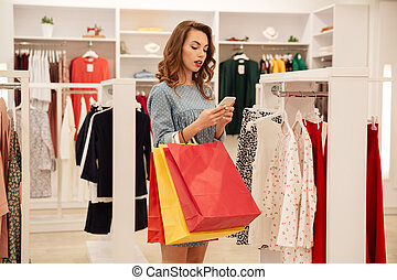 Young woman with packages using smartphone