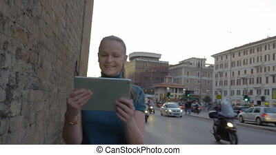 Young woman with pad having video chat outdoor