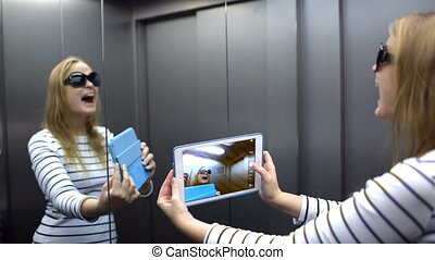 Young woman with pad in the lift posing and taking pictures