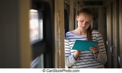 Young woman with pad standing by the window in train hallway