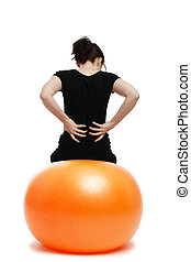 young woman with pain in the back sitting on orange exercise ball