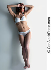 young woman with perfect body in white lingerie