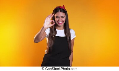 Young woman with perfect make-up making OK sign over yellow background. Winner. Success. Positive girl smiles to camera. Body language.