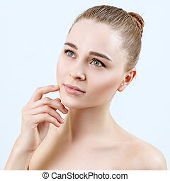 Young woman with perfect skin dreaming over blue background.