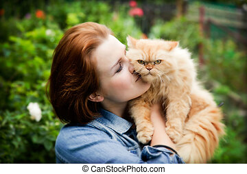 Young woman with Persian cat playing. Outdoors portrait