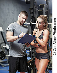young woman with personal trainer in gym - fitness, sport,...