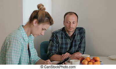Young woman with phone and man sitting at table in kitchen...