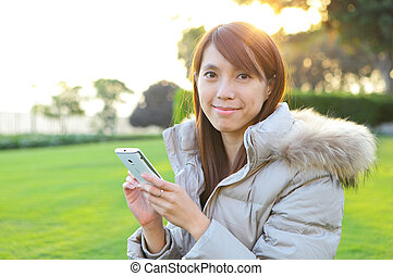 young woman with phone outdoors