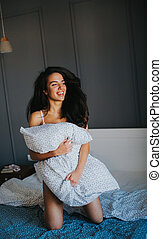 Young woman with pillow on bed