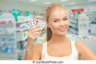young woman with pills in drugstore or pharmacy
