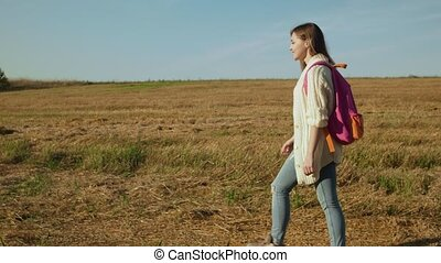 Young woman with pink backpack walking in autumn rural...