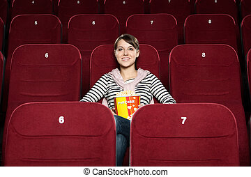 Young woman with popcorn in the movie theater