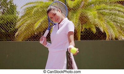 Young Woman with Racket and Ball on Tennis Court