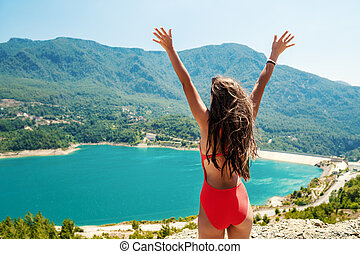 woman with raised up hands standing on the top of rock