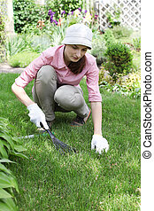 Young woman with rake working in the garden bed