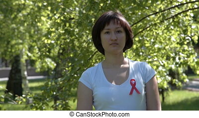 Young woman with red awareness ribbon