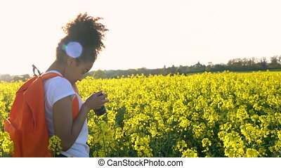 Young woman with red backpack and camera taking photograph...