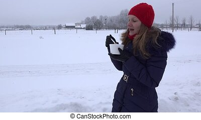 woman with red cap eat hot soup outdoor at cold winter time....
