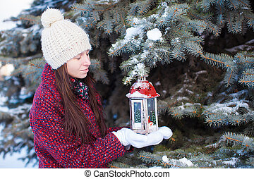 Young woman with red Christmas lantern in the snow