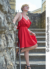 young woman with red dress on steps