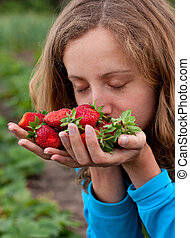 Young woman with red fresh strawberries in hands