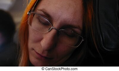 Young woman with red hair and glasses sleeping in a flying aircraft, then wake up and smiling