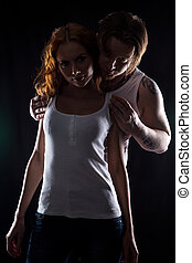 Young woman with red hair and hugging man