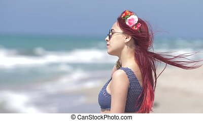 young woman with red hair flying in the wind and a floral wreath in her hair against the background of the sea