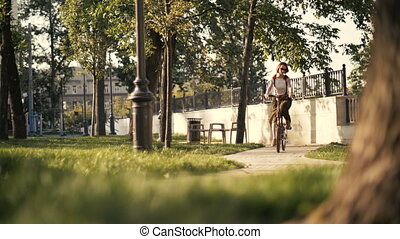 Young woman with red hair riding a bike in park bottom view....