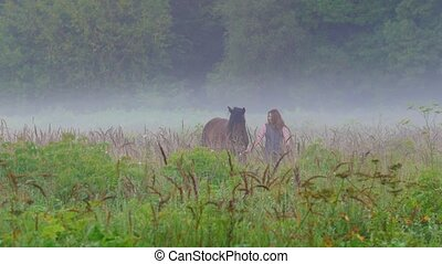 Young woman with red hair walks with a horse of brown color on the field in the fog
